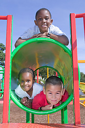Three children playing on a climbing frame together at the playground,