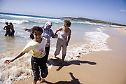 New Iraqi Migrants and their Jewish advocate<br /> Twin sisters from Iraqi , Hawra and Zainab with their mother Bahja have just seen and entered the ocean for first time in their lives. <br /> Judi McLallan a Jewish volunteer advocate for the family leads them out of the water after spontaneous dip and splash at Maroubra Beach on their first morning in Sydney after arriving from the middle east.