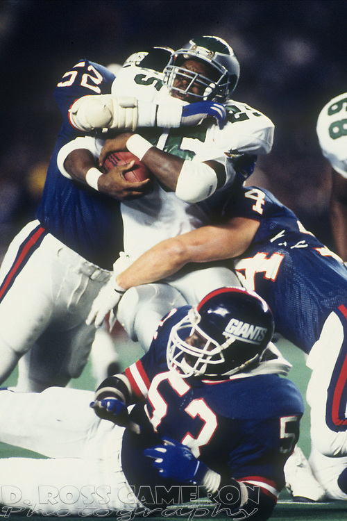 New York Giants defenders Pepper Johnson (52) Andy Headen (54) and Harry Carson (53) wrap up Philadelphia Eagles running back Anthony Toney during an NFL football game, Monday, Oct. 10, 1988 at Veterans Stadium in Philadelphia, Pa. The Eagles won, 24-13. (Photo by D. Ross Cameron)