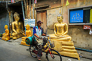 """12 NOVEMBER 2012 - BANGKOK, THAILAND:   A man bicycles past statues of the Buddha on Bamrung Muang Street in Bangkok. Thanon Bamrung Muang (Thanon is Thai for Road or Street) is Bangkok's """"Street of Many Buddhas."""" Like many ancient cities, Bangkok was once a city of artisan's neighborhoods and Bamrung Muang Road, near Bangkok's present day city hall, was once the street where all the country's Buddha statues were made. Now they made in factories on the edge of Bangkok, but Bamrung Muang Road is still where the statues are sold. Once an elephant trail, it was one of the first streets paved in Bangkok. It is the largest center of Buddhist supplies in Thailand. Not just statues but also monk's robes, candles, alms bowls, and pre-configured alms baskets are for sale along both sides of the street.    PHOTO BY JACK KURTZ"""