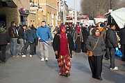People from various ethnic backgrounds around the market on Whitechapel High Street in East London. This area in the Tower Hamlets is predominantly Muslim with just over 50% of Bangladeshi descent. This is known as a very Asian and increasingly African and multi cultural part of London's East End.