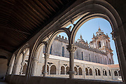 Seen through restored cloister pillars of the cloister of Dom Dinis, is the main church of Alcobaca Monastery (Mosteiro de Santa Maria de Alcobaca), on 16th July, at Alcobaca, Portugal. The monastery was completed in 1223 for the Cistercian order and added to further by King Dinnis (Dennis) who built the main cloister and is now a UNESCO World Heritage Site. Austere architecture is in keeping with the Cistercian regard for simplicity. (Photo by Richard Baker / In Pictures via Getty Images)