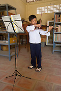 Bunroeun is taught classical violin at the Phnom Penh school of 'Beaux Arts' outside Phnom Penh..A Khmer boy learns to play classical violin at the school of Beaux Arts, at the edge of Cambodia's capital, Phnom Penh. He is an orphan and comes from a poor family. His parents died long ago, from AIDS related diseases. He lives with his grandmother and his uncle, and their family. He lives on the top floor of an apartment block, where his family run a textile business, sewing together clothes and ornamental flags from around the world. A dozen young women work in this textile business, and the boy's home space is actually amidst this small factory environment which he shares with them. They eat, work and play together like an extended family or community. Phnom Penh, Cambodia