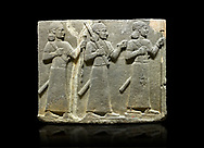 Hittite relief sculpted orthostat stone panel of Royal Buttress Basalt, Karkamıs, (Kargamıs), Carchemish (Karkemish), 900-700 B.C. Warriors. Anatolian Civilisations Museum, Ankara, Turkey.<br /> Three figures each with a long dress, a thick belt and curly hair. The figure in front holds a spear with a broken tip in his left hand and a leafy branch in his right hand. The figure in the middle made his left hand a fist, and he carries a tool with his right hand at the level of his head. They are followed with a figure holding a sceptre in his left hand. All three have each a long sword at their waist.<br /> <br /> Against a black background. .<br />  <br /> If you prefer to buy from our ALAMY STOCK LIBRARY page at https://www.alamy.com/portfolio/paul-williams-funkystock/hittite-art-antiquities.html  - Type  Karkamıs in LOWER SEARCH WITHIN GALLERY box. Refine search by adding background colour, place, museum etc.<br /> <br /> Visit our HITTITE PHOTO COLLECTIONS for more photos to download or buy as wall art prints https://funkystock.photoshelter.com/gallery-collection/The-Hittites-Art-Artefacts-Antiquities-Historic-Sites-Pictures-Images-of/C0000NUBSMhSc3Oo