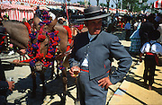 """A carriage driver dressed in tradional """"traje corto"""", sips his beer, with casetas behind..The Feria de abril de Sevilla, """"Seville April Fair"""" dates back to 1847. During the 1920s, the feria reached its peak and became the spectacle that it is today. It is held in the Andalusian capital of Seville in Spain. The fair generally begins two weeks after the Semana Santa, Easter Holy Week. The fair officially begins at midnight on Monday, and runs six days, ending on the following Sunday. Each day the fiesta begins with the parade of carriages and riders, at midday, carrying Seville's citizens to the bullring, La Real Maestranza...For the duration of the fair, the fairgrounds and a vast area on the far bank of the Guadalquivir River are covered in rows of casetas (individual decorated marquee tents which are temporarily built on the fairground). Some of these casetas belong to the prominent families of Seville, some to groups of friends, clubs, trade associations or political parties. From around nine at night until six or seven the following morning, at first in the streets and later only within each caseta, crowds of people party and dance Sevillanas, traditional Flamenco dances, Sevillan style drinking Jerez sherry, or Manzanilla wine, and eating tapas. Men and women dress up in their finery, the traditional """"traje corto"""" (short jacket, tight trousers and boots) for men and the """"faralaes"""" or """"trajes de flamenca"""" (flamenco style dress) for women. The men traditionally wear hats called """"cordobés""""."""