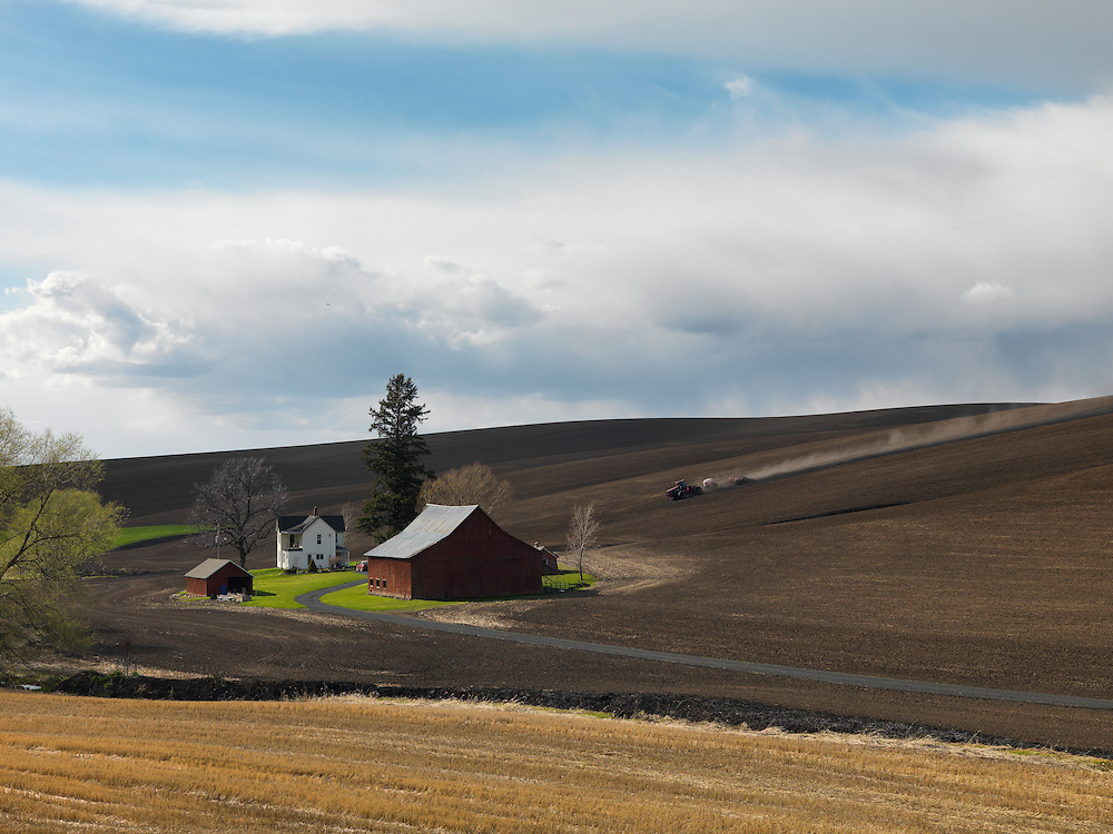 Agriculture mecca of the Washington State Palouse with farm yard and tractor plowing rolling hills in Springtime.  Open Edition Prints and Editorial Licensing.
