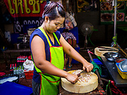 """18 MAY 2017 - BANGKOK, THAILAND: A vendor cuts up garlic at the food stall Bangkok's Chinatown. City officials in Bangkok have taken steps to rein in street food vendors. The steps were originally reported as a """"ban"""" on street food, but after an uproar in local and international news outlets, city officials said street food vendors wouldn't be banned but would be regulated, undergo health inspections and be restricted to certain hours on major streets. On Yaowarat Road, in the heart of Bangkok's touristy Chinatown, the city has closed some traffic lanes to facilitate the vendors. But in other parts of the city, the vendors have been moved off of major streets and sidewalks.      PHOTO BY JACK KURTZ"""