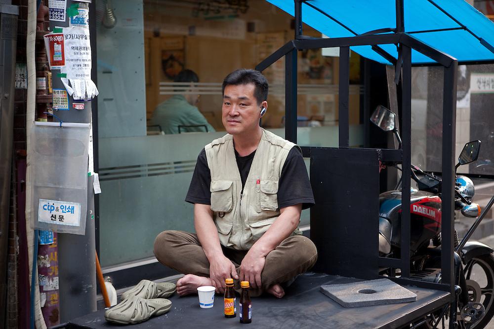 Mann ruht sich vor einer Druckerei auf der Ladefläche eine Motorrads aus.<br /> <br /> Man relaxing infront of a print shop on a load platform of a motorcycle in the center of the korean capital Seoul.