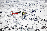 Shad O'Neel, glaciologist with the USGS, flies off in a helicopter above the Columbia Glacier, near Valdez, Alaska, to deploy GPS rovers on the glacier surface to measure surface velocities.