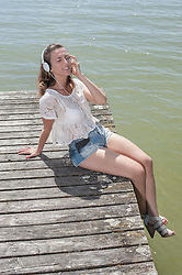 Woman listening to music and sitting on boardwalk at the lake, Ammersee, Upper Bavaria, Germany