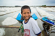 24 APRIL 2013 - SAMUT SONGKHRAM, SAMUT SONGKHRAM, THAILAND:   A child who works in the salt fields around Samut Songkhram, Thailand, waits for his work assignment during the 2013 salt harvest. The 2013 salt harvest in Thailand and Cambodia has been impacted by unseasonably heavy rains. Normally, the salt fields are prepped for in December, January and February, when they're leveled and flooded with sea water. Salt is harvested from the fields from late February through May, as the water evaporates leaving salt behind. This year rains in December and January limited access to the fields and rain again in March and April has reduced the amount of salt available in the fields. Thai salt farmers are finishing the harvest as best they can, but the harvest in neighboring Cambodia ended 6 weeks early because of rain. Salt has traditionally been harvested in tidal basins along the coast southwest of Bangkok but industrial development in the area has reduced the amount of land available for commercial salt production and now salt is mainly harvested in a small part of Samut Songkhram province.    PHOTO BY JACK KURTZ