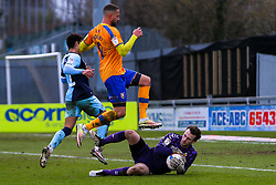 Jordan Bowery of Mansfield Town hurdles a diving save by Callum Burton of Cambridge United - Mandatory by-line: Ryan Crockett/JMP - 20/02/2021 - FOOTBALL - One Call Stadium - Mansfield, England - Mansfield Town v Cambridge United - Sky Bet League Two