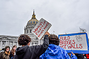 """Two young children stand among the crowd gathering before San Francisco City Hall with signs reading, """"Womens rights are human rights,"""" and """"Build bridges not walls."""""""
