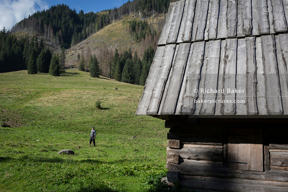 A mountain farmer walks past an agricultural hut on Polana Chocholowska a hiking route on Dolina Chocholowska in the Tatra National Park, on 17th September 2019, near Zakopane, Malopolska, Poland.