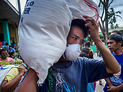 24 JANUARY 2018 - GUINOBATAN, ALBAY, PHILIPPINES:  An evacuee wearing a breathing filter because of the volcanic ash fall picks up a sack of donated supplies at the Barangay Maninila Evacuation Center in Guinobatan East Central School. The Mayon volcano continued to erupt Tuesday night and Wednesday forcing the Albay provincial government to order more evacuations. By Wednesday evening (Philippine time) more than 60,000 people had been evacuated from communities around the volcano to shelters outside of the 8 kilometer danger zone. Additionally, ash falls continued to disrupt life beyond the danger zones. Several airports in the region, including the airport in Legazpi, the busiest airport in the region, are closed indefinitely because of the amount of ash the volcano has thrown into the air.   PHOTO BY JACK KURTZ