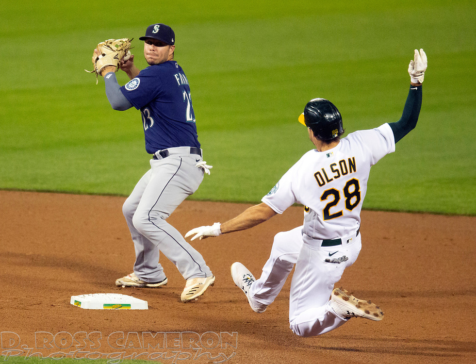 Sep 25, 2020; Oakland, California, USA; Seattle Mariners second baseman Ty France (23) prepares to throw over Oakland Athletics baserunner Matt Olson (28) to complete a double play during the fourth inning of a Major League Baseball game at Oakland Coliseum. Khris Davis was out at first base. Mandatory Credit: D. Ross Cameron-USA TODAY Sports