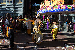 © Licensed to London News Pictures. 24/01/2016 Ipoh, Malaysia. A devotee with metals hooks pieced on his back and a devotee carrying a kavadi dance as they arrive at Kallumalai Murugan Temple in Ipoh, Malaysia, during the Thaipusam Festival, Sunday, Jan. 24, 2016. Photo credit : Sang Tan/LNP