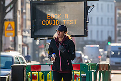 © Licensed to London News Pictures. 22/01/2021. London, UK. A member of the public runs past a Covid-19 information sign in Fulham South West London as the government downplays the idea of a universal £500 covid payment for those who self-isolate. A leaked government document suggested giving £500 to anyone who tested positive for coronavirus as death rates continue to rise in England. Photo credit: Alex Lentati/LNP
