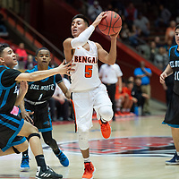 """Gallup Bengals Seth Manuelito (5) at the top of the key, looks for an open teammate with two Del Norte Knights defenders near by during the NMAA State Tournament. The Knights defeated the Bengals 55-49 at """"The Pit"""" in Albuquerque Wednesday evening."""