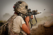 U.S. Army Sergeant Rolando Zavala fires over the walls of Combat Outpost Nolen during a firefight with the Taliban.