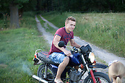 Polish teen age 18 riding his motorcycle on country dirt road. Zawady Central Poland