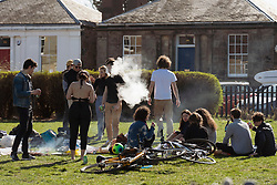 Portobello, Scotland, UK. 3 April 2021. Easter weekend crowds descend on Portobello beach and promenade to make the most of newly relaxed  Covid-19 lockdown travel restrictions and warm sunshine with uninterrupted blue skies. Pic;  Group of young people with barbecue and drinks on the promenade. Iain Masterton/Alamy Live News