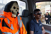 Man in a van sitting next to a dressed up skeleton in the passenger seat. Halloween fun with a skull in a high viz jacket. London, UK.