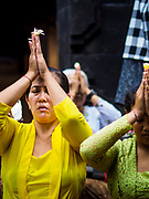 """08 AUGUST 2017 - UBUD, BALI, INDONESIA: Family members pray during a ceremony to honor a family temple in Ubud, Bali. Balinese Hindus have a 210 day calender and every almost every family compound on Bali has a family temple. Once a year (or every 210 days) families celebrate the """"birthday"""" of their temple with a ceremony.     PHOTO BY JACK KURTZ"""