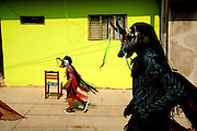"""""""Los Chivos"""", or goats, dance the streets in a procession in honor of Santa Cruz during the fiestas of Acatlán, Mexico.  In early May the people of this small community leave offering for Santa Cruz.  They also maintain the ancient tradition of fighting in jaguar masks. This is a pre-Columbian tradition in which the blood and sweat that fall to the ground are an offering to earth.  In return for their blood the people ask the gods for rain."""