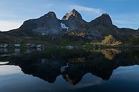 Reflection of mountain peaks rising above isolated village of Kirkefjord, near Reine, Moskenesøy, Lofoten Islands, Norway
