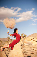 Mysterious female wearing a red dress holding a tumbleweed in the desert.