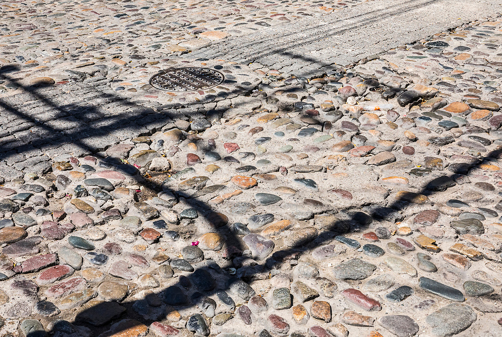 Shadows of utility poles and lines on the rock and concrete streets of old Puerto Vallarta, Jalisco, Mexico.