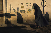 Kabul 2001. Woman in a burqa walking past a wall drawing showing different sorts of landmines and other weapons.