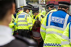 London, UK. 6 September, 2019. Metropolitan Police officers arrest climate activists who had locked themselves together using an arm tube in one of the two main access roads to ExCel London on the fifth day of a week-long carnival of resistance against DSEI, the world's largest arms fair. The road remained blocked for several hours. The fifth day of protests was themed as Stop The Arms Fair: Stop Climate Change in order to highlight links between the fossil fuel and arms industries.