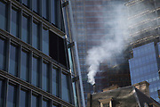 Pollution from the chimney of an old building pours out into the atmosphere amongst modern glass buildings in the City of London, London, England, United Kingdom. At street level emissions add up to the poor air quality which people are breathing on a daily basis. London is trying to achieve air quality targets. The European Air Quality Index, run by the European Environment Agency EEA and the European Commission, allows users to check the current air quality across Europe's cities and regions. Environmental groups called for the Government to take urgent steps, including creating and funding clean air zones in pollution hotspots.
