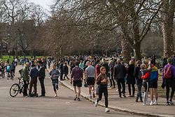 © Licensed to London News Pictures.20/02/2021. London, UK. Members of the public enjoy walking through Victoria Park in east London. The weather forecasts predict that it will be the warmest weekend since November.  Photo credit: Marcin Nowak/LNP