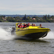 People enjoy the speed and spins and the adrenaline rush of the Kawarau Jet boat on Lake Rotorua.  The half hour thrill ride also includes passing historical landmarks of  Mokoia Island, the Sacred Island and the world renowned Sulphur Lake. Rotorua .New Zealand. 11th December 2010. Photo Tim Clayton.