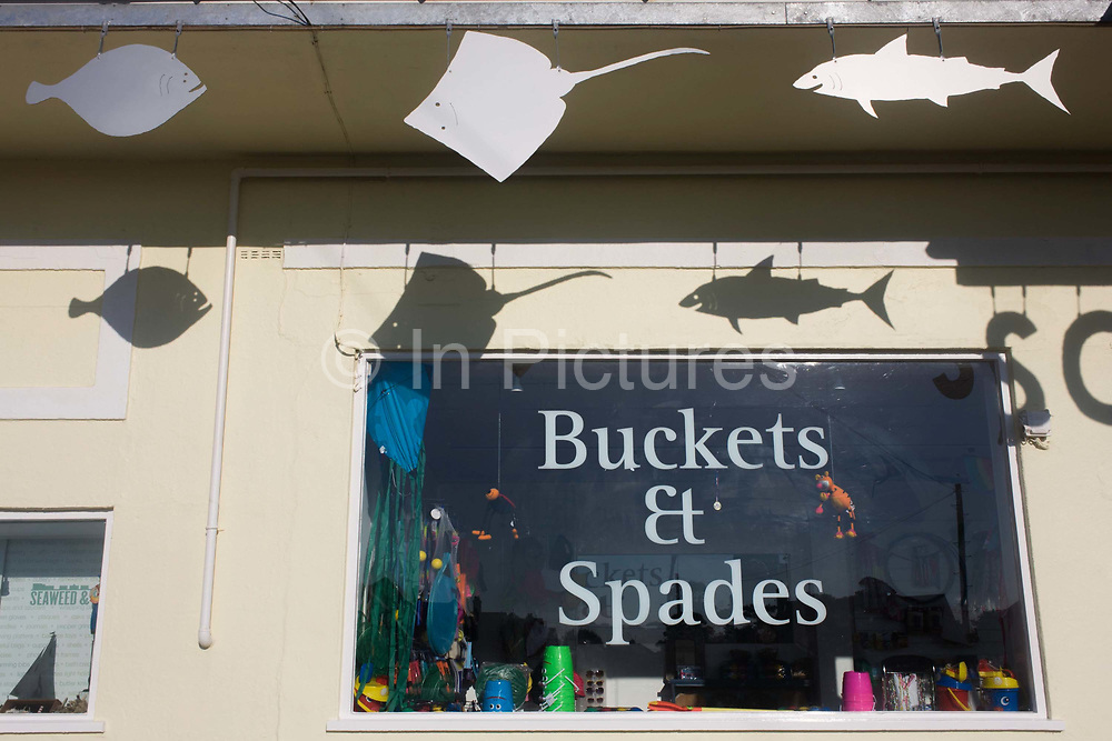 A beach shop and fish sign shadows at the Suffolk seaside town of Southwold, Suffolk, known for its lack of branded commercialism. The words 'Buckets and Spades' have been stenciled on the window of this shop on the seafront. Southwold is a small town on the North Sea coast, in the Waveney district of the English county of Suffolk. It is located on the North Sea coast at the mouth of the River Blyth within the Suffolk Coast and Heaths Area of Outstanding Natural Beauty. The town is around 11 miles (18 km) south of Lowestoft and 29 miles (47 km) north-east of Ipswich.