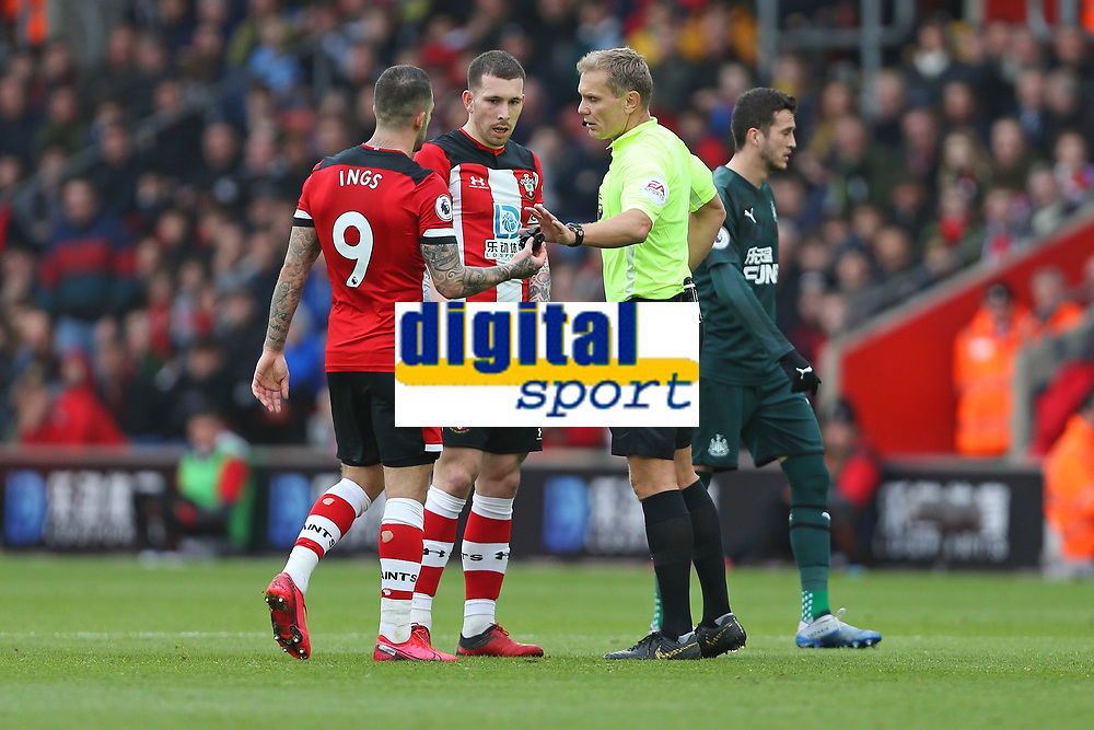 Football - 2019 / 2020 Premier League - Southampton vs. Newcastle United<br /> <br /> In the the drama of VAR and red card Referee Mr Graham Scott dropped his whistle so Southampton's Danny Ings picked it up and returned it to the official during the Premier League match at St Mary's Stadium Southampton  <br /> <br /> COLORSPORT/SHAUN BOGGUST