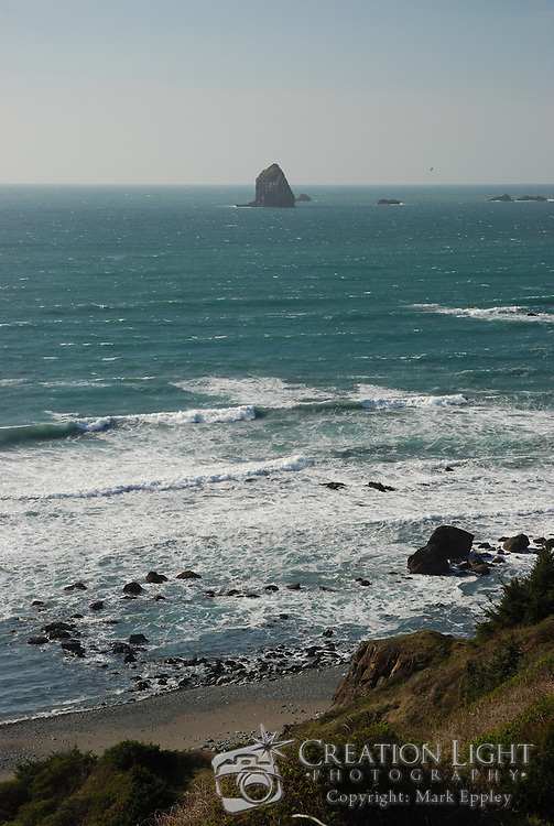 The Oregon coast is marked with rocks that rise above the ocean's surface, some small as seen in near the beach here and some massive as seen in the distance.