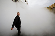 "Brewmaster Joachim Rösch walks into a cloud of steam outside a factory at the Ganter Brewery in Freiburg im Breisgau, Germany.  (Joachim Rösch  is featured in the book What I Eat: Around the World in 80 Diets.)  The caloric value of his day's worth of food in March was 2700 kcals. He is 44 years of age; 6 feet, 2 inches tall; and 207 pounds. Joachim's job requires him to taste beer a number of times during the week, and unlike in wine tasting, he can't just taste then spit it out: ""Once you've got the bitter on the back of your tongue, you automatically get the swallow reflex, so down the chute you go,"" he says. MODEL RELEASED."