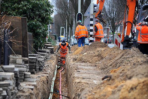 Nederland, Nijmegen, 25-2-2010Grondwerkers trekken een nieuwe stroomkabel in de wijk Brakkenstein. Door beschadiging van een transformatorhuisje moest de hele kabel vervangen worden. In de sleuf liggen ook glasvezelkabels en telefoonkabels.Foto: Flip Franssen/Hollandse Hoogte