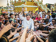 06 JANUARY 2013 - BANGKOK, THAILAND:  People reach for Buddhist amulets recently blessed by monks after a service for a relic that is a piece of the Buddha's hair. The relic has been on display in Bangkok for about 10 years. There was a ceremony in Sanam Luang in Bangkok Sunday to honor the relic. People prayed for it and received blessings from Buddhist monks and Brahmin priests who presided over the service. The hair is being moved to Ayutthaya, where it will be displayed in a Buddhist temple. The piece of hair has been on loan to Thai Buddhists from a Buddhist temple in Sri Lanka.   PHOTO BY JACK KURTZ