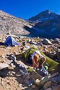 Climber in camp at Dade Lake under Bear Creek Spire, John Muir Wilderness, Sierra Nevada Mountains, California