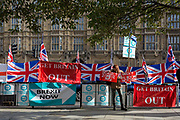 On the day that the EU in Brussels agreed in principle to extend Brexit until 31st January 2020 aka Flextension and not 31st October 2019, a Brexiteer stands next to Brexit Party flags and banners during a Brexit protest outside parliament, on 28th October 2019, in Westminster, London, England.