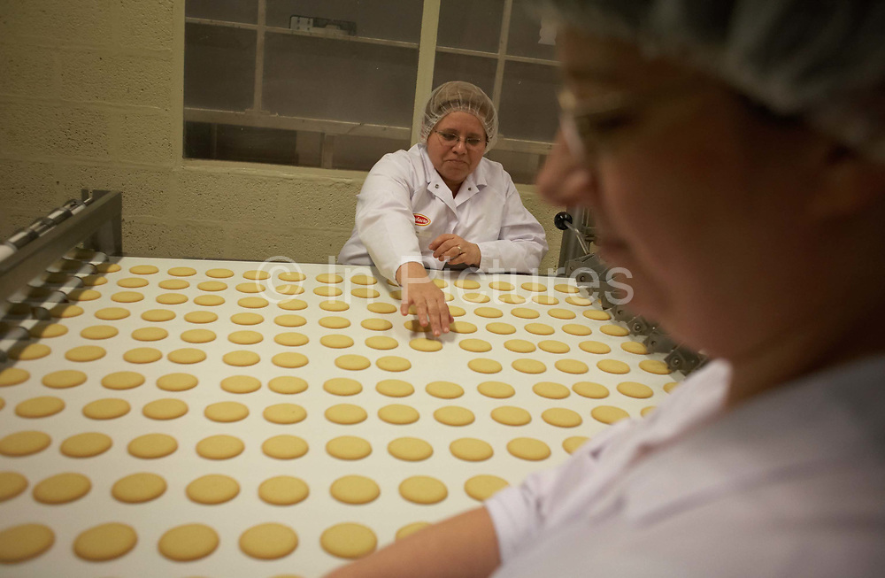 A lady employee of Delacre Biscuits sorts through sub-standard product from rows of steadily moving, freshly-produced biscuits on the conveyor belt at the company factory at Lambermont, near Liege, southern Belgium. Seated opposite a colleague also dressed in white overall and hair net, both women concentrate on the job, removing the snacks that fail quality control for whatever reason means the biscuit is unfit for sale. The biscuits are from the Moments range created by McVitie's, the British company owned by United Biscuits. Multitudes of these snacks are manufactured before export across Europe. Delacre Biscuits is a subsidiary of United Biscuits having been making biscuits since Brussels pharmacist Charles Delacre decided to sell chocolate in 1870, which was then regarded as a medicinal tonic.