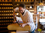 Shopkeeper cutting cheese in cheese shop and warehouse, Zuiderzee museum, Enkhuizen, Netherlands