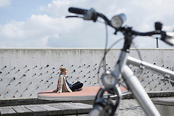 Young woman in theme park with bike in foreground, Munich, Bavaria, Germany