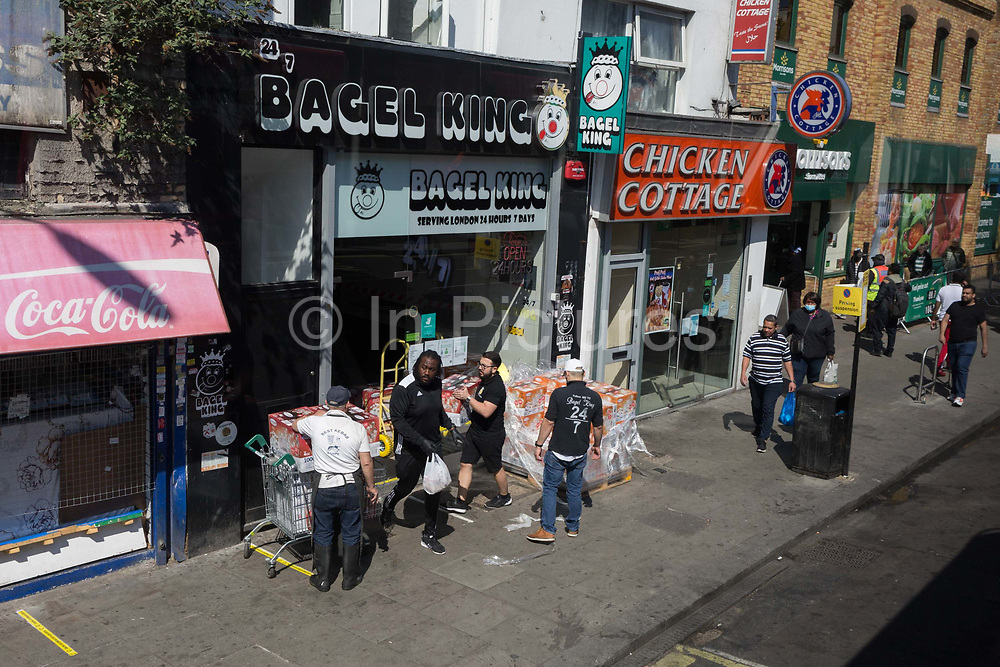 As the UKs Coronavirus death toll during the governments social distancing lockdown, rose by 384 to 33,998, and the R rate of infection is reported to be between 0.7 and 1.0, south Londoners go about their business on the Walworth Road in Southwark, on 15th May 2020, in London, England.