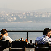 Tourists enjoy sipping on their Turkish tea while enjoying a view over the Bosphorus in Gulhane Park next to the Topkapi Palace.